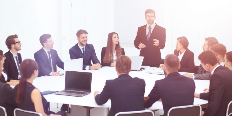 Director of the company discussing work problems at the meeting and points a finger at one of the employees.staff listen attentively to the Director and record information in notebooks